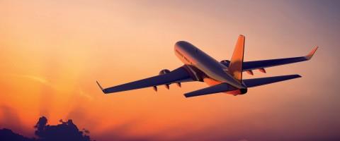 Vliegtuig wat oranje lug vlieg